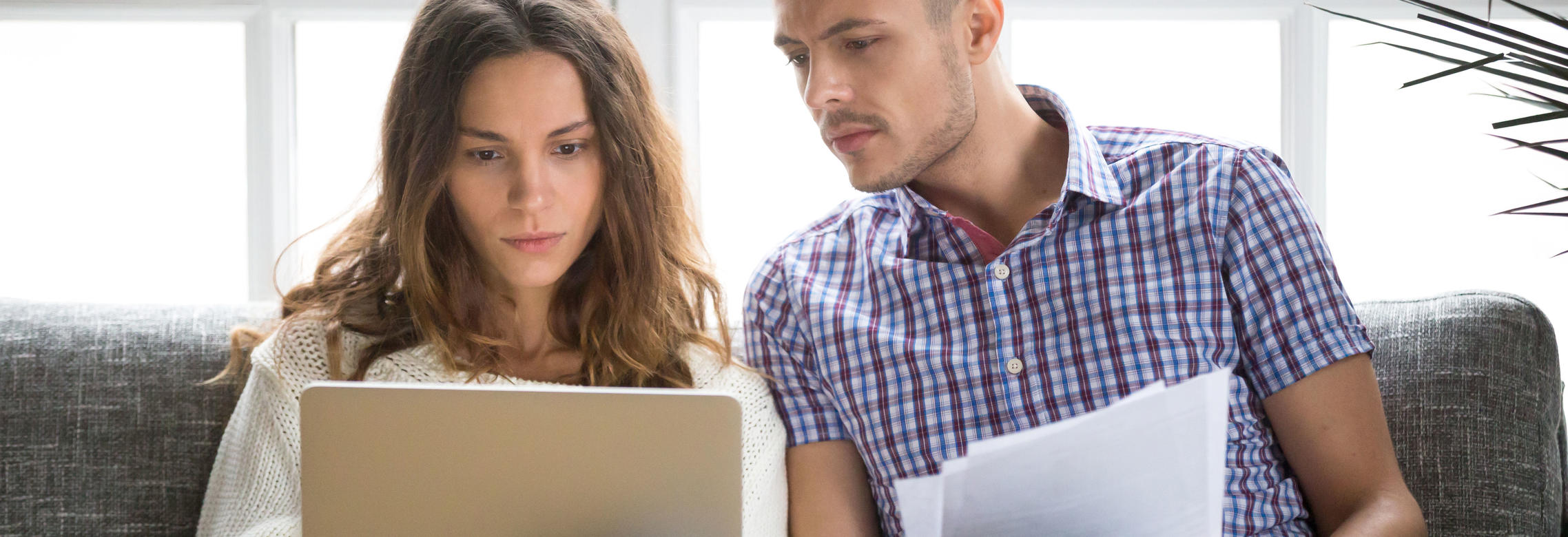 Focused worried couple paying bills online on laptop with documents