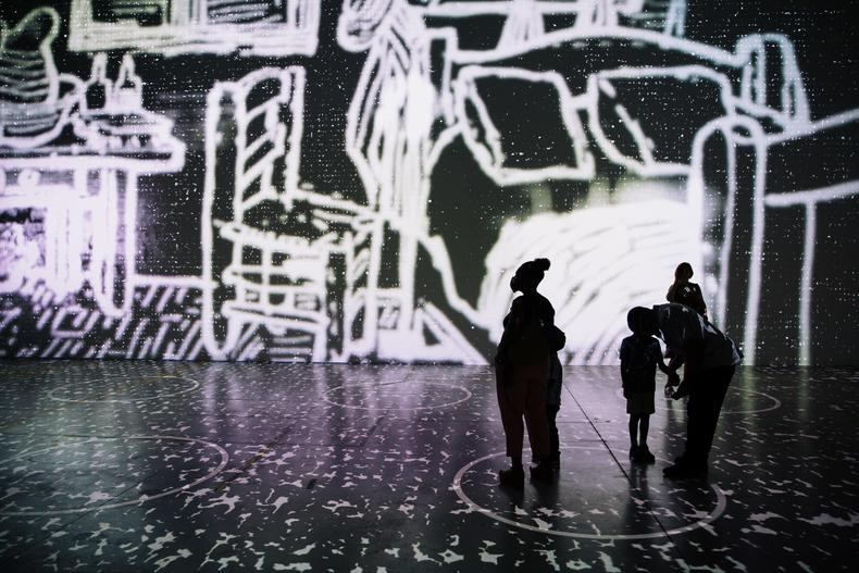 a family stands silhouetted by the projections of the van gogh exhibit
