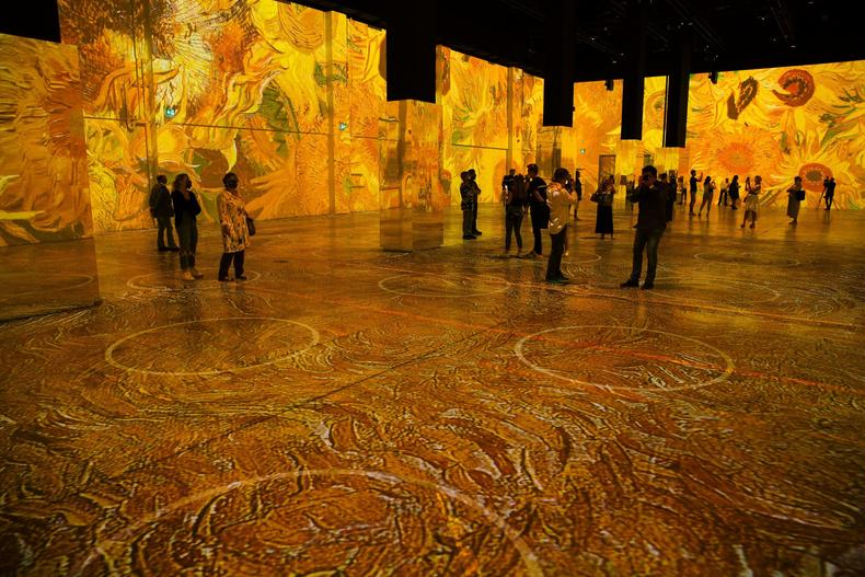 visitors view the immersive van gogh exhibit in the open space of the room