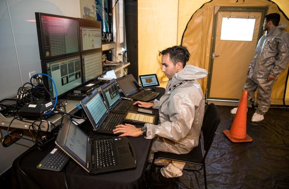 Man in command center with Panasonic TOUGHBOOK laptops and TV monitor