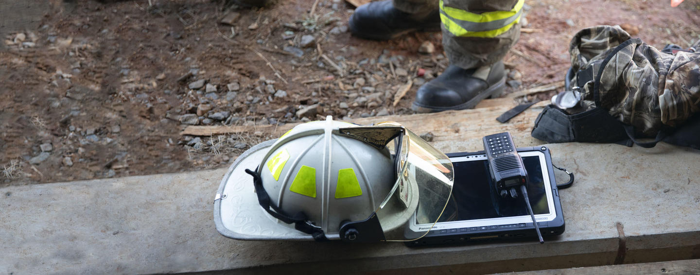Feet of fireman with helmet TOUGHBOOK tablet and radio on boards