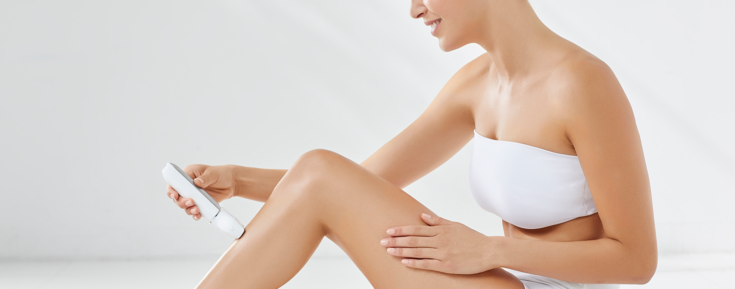 Woman sitting, wrapped in a white towel while shaving her legs.