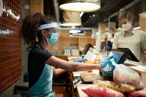 a cashier in protective gear rings up a customer at a grocery store