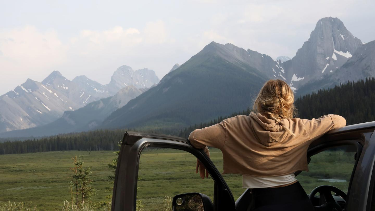 Green Living Young woman stops driving to relax and enjoy the view