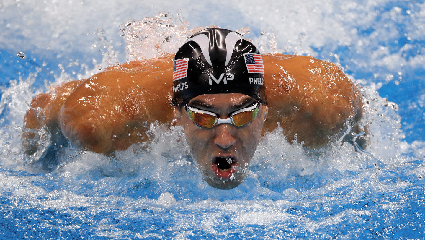 Michael Phelps with swim cap and goggles crashing through the water.