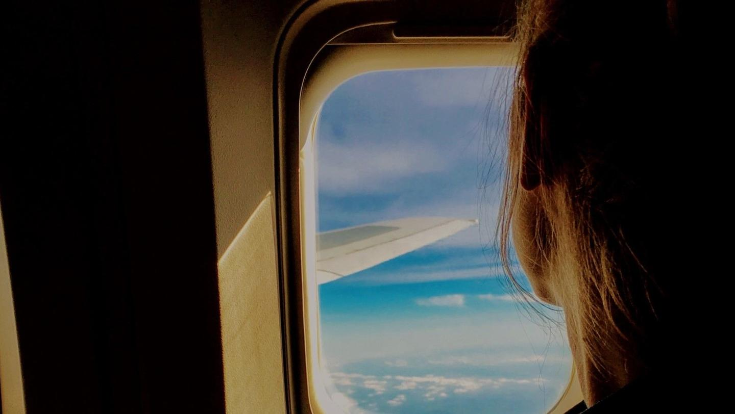 a woman looks out an airplane window