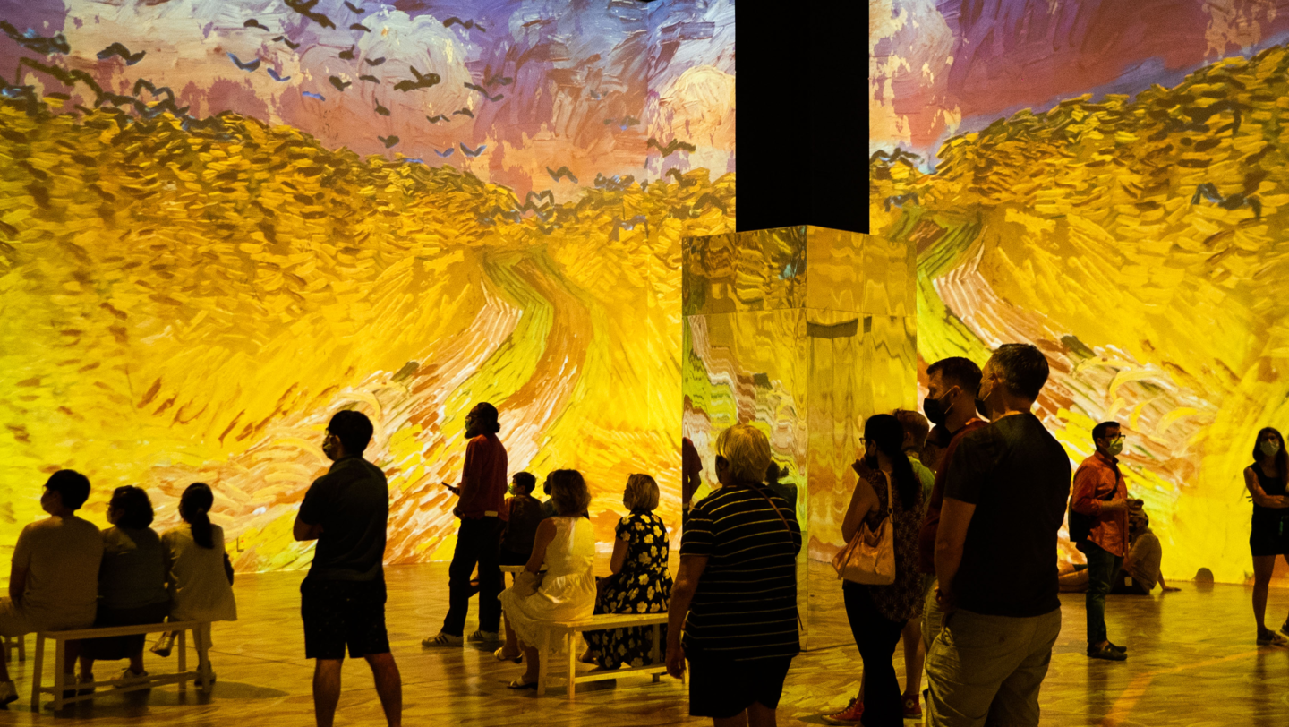 Socially distanced groups stand amidst an immersive Van Gogh experience