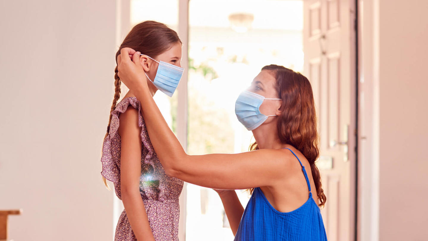 a woman puts a mask on her child