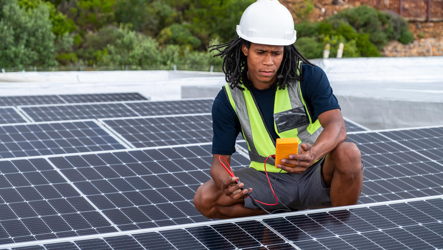 African man installing solar panels on a roof of a house