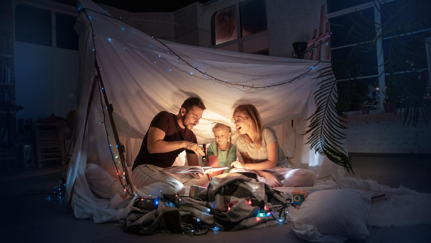 Caucasian family sitting in a teepee, reading stories with the flashlight in dark room with toys and pillows. Caucasian models. Home comfort, family, love, Christmas holidays, storytelling time.