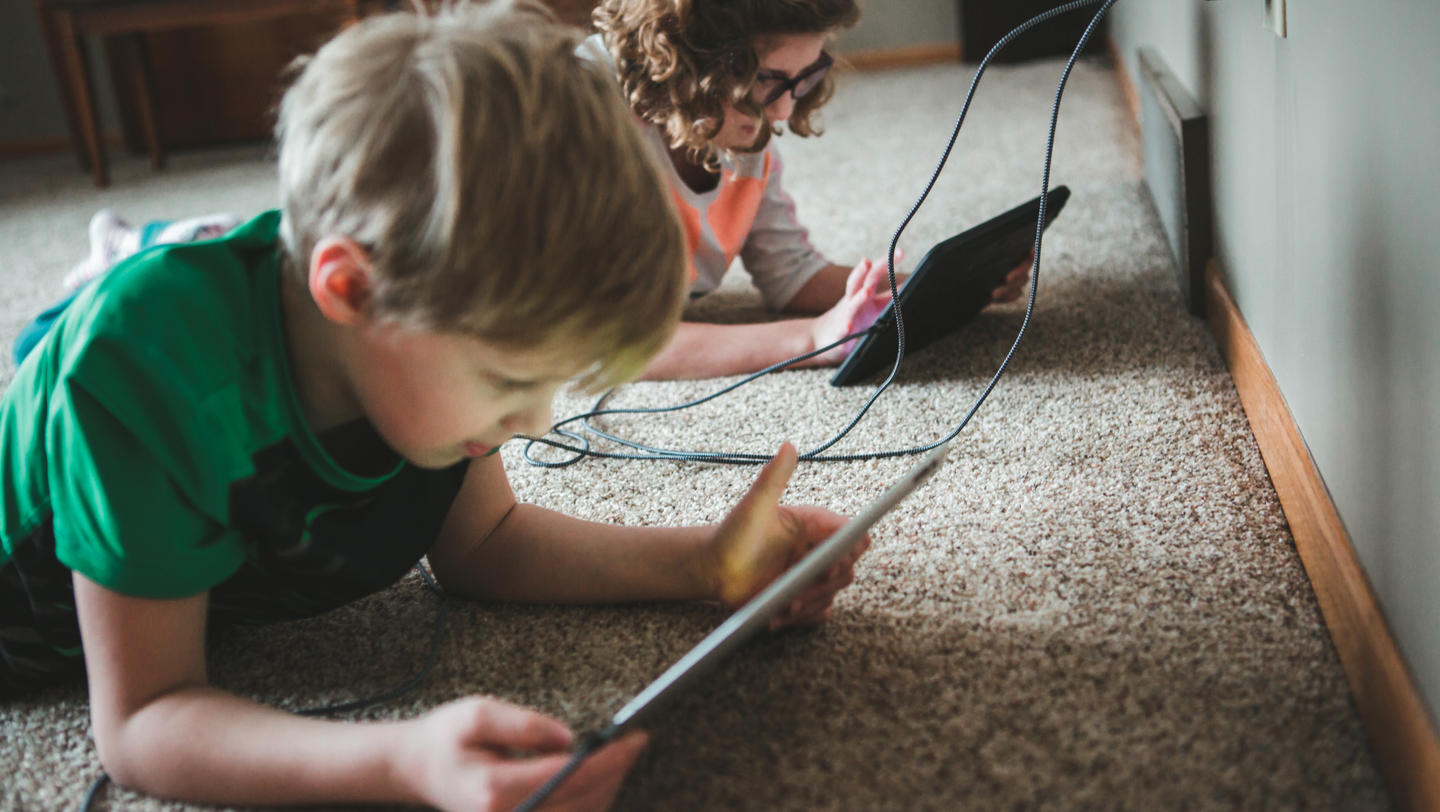 Children using tablets plugged into a dual charger