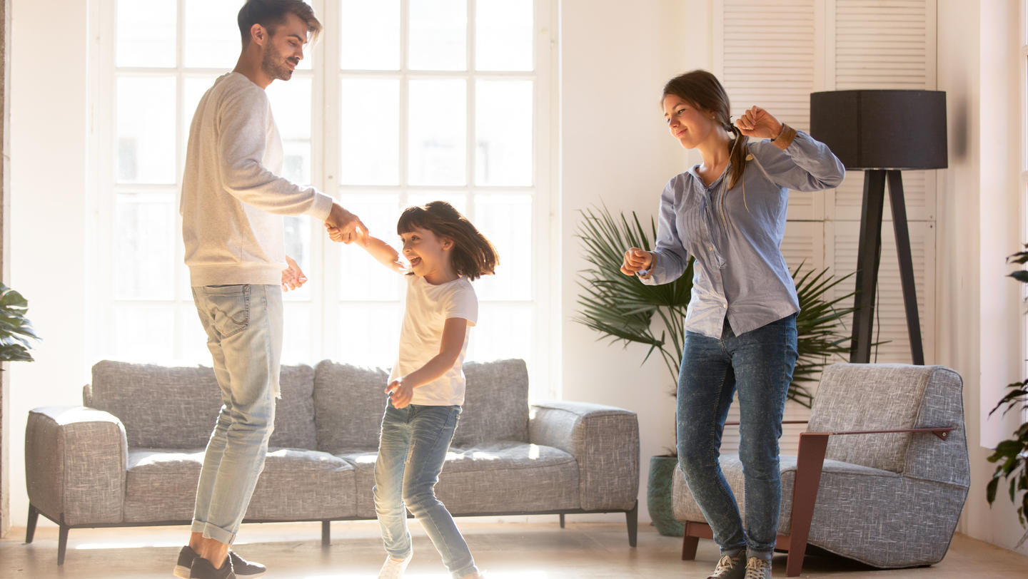 Family dancing in living room spending time on weekend together