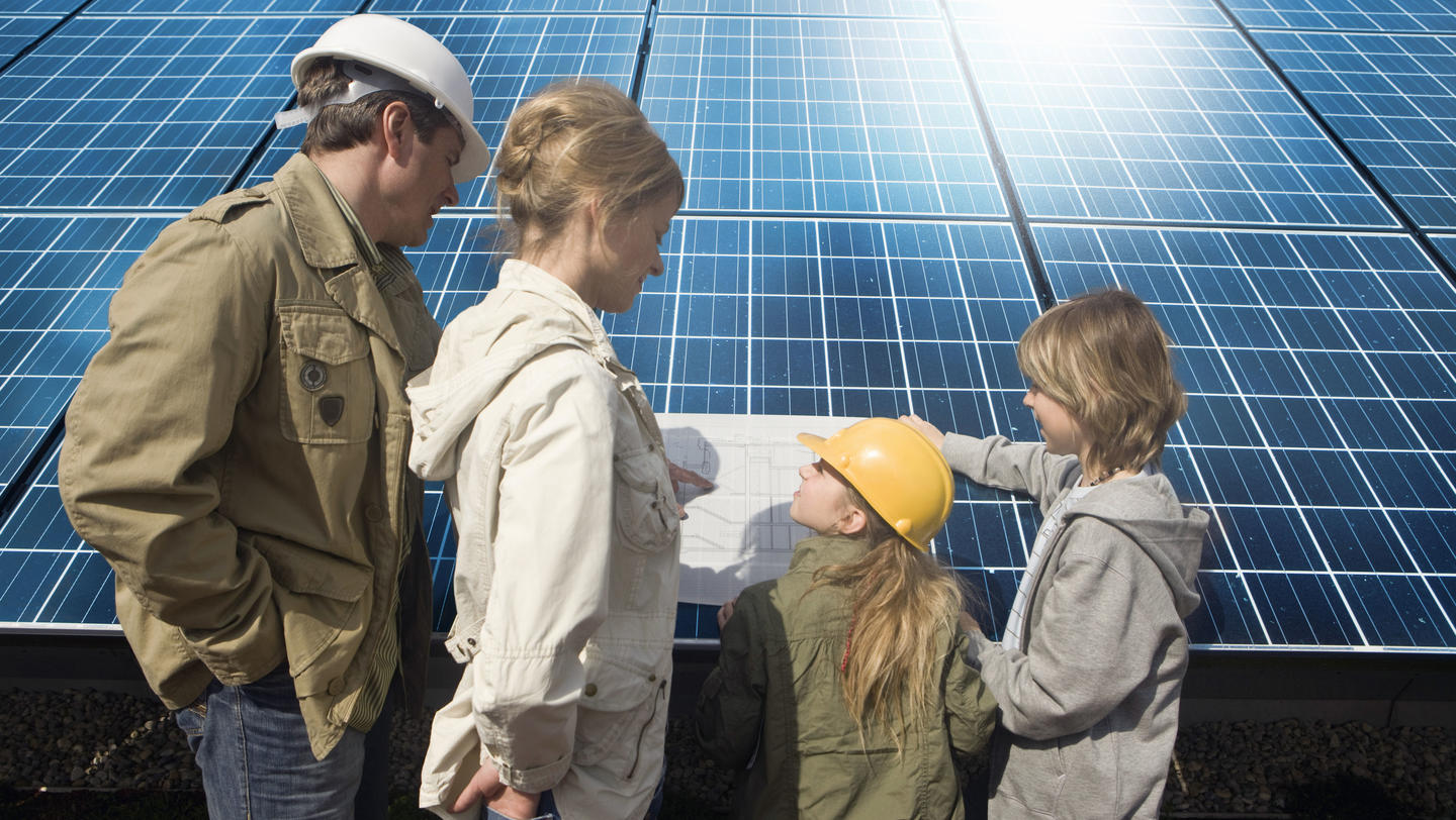Family standing by solar panels looking at plans