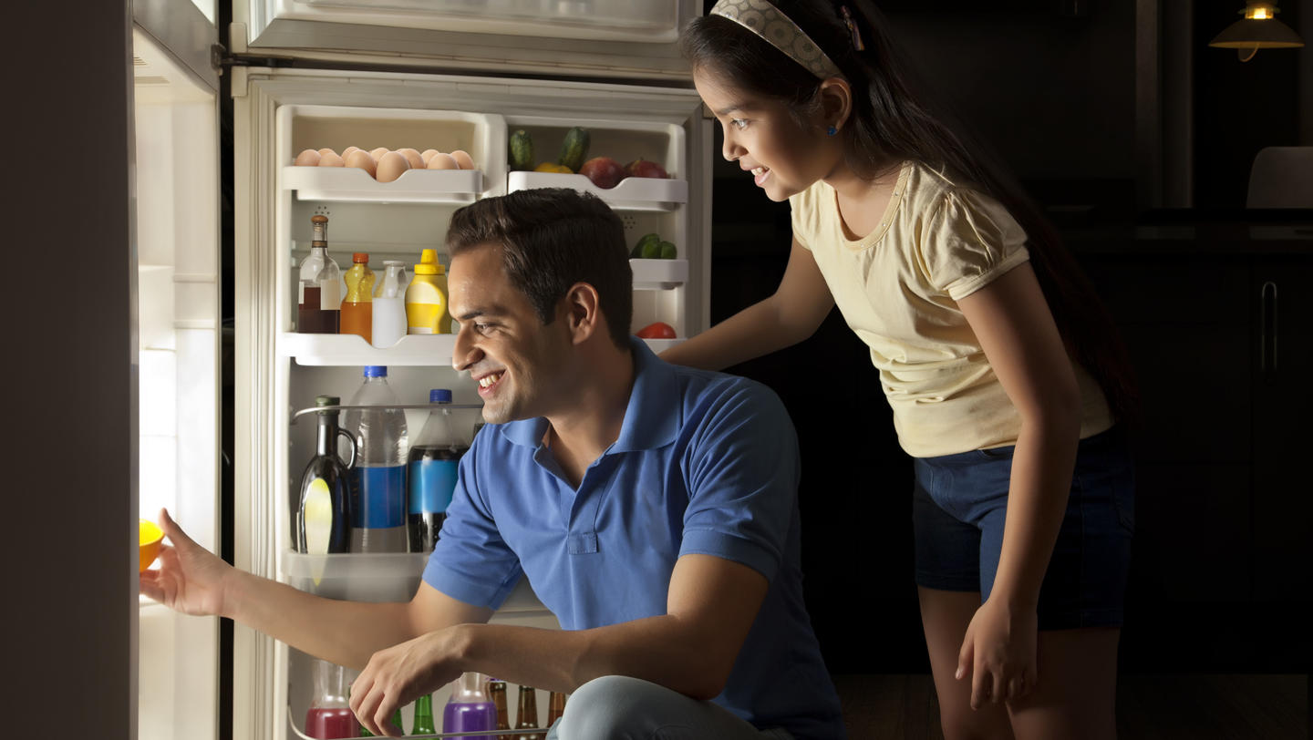 Father and daughter keeping food in refrigerator at night
