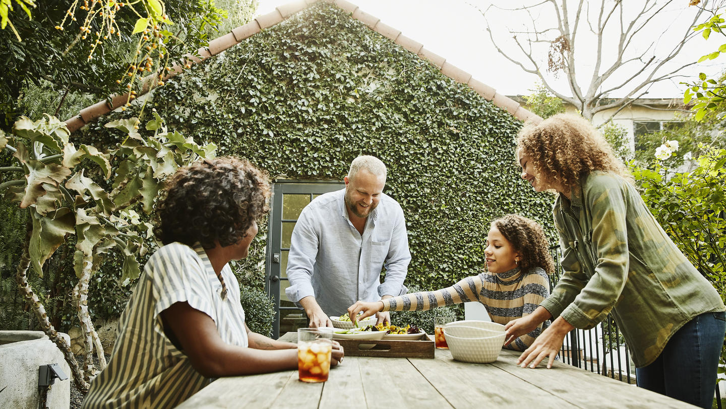 Father bringing try of food to family sitting at picnic table in backyard