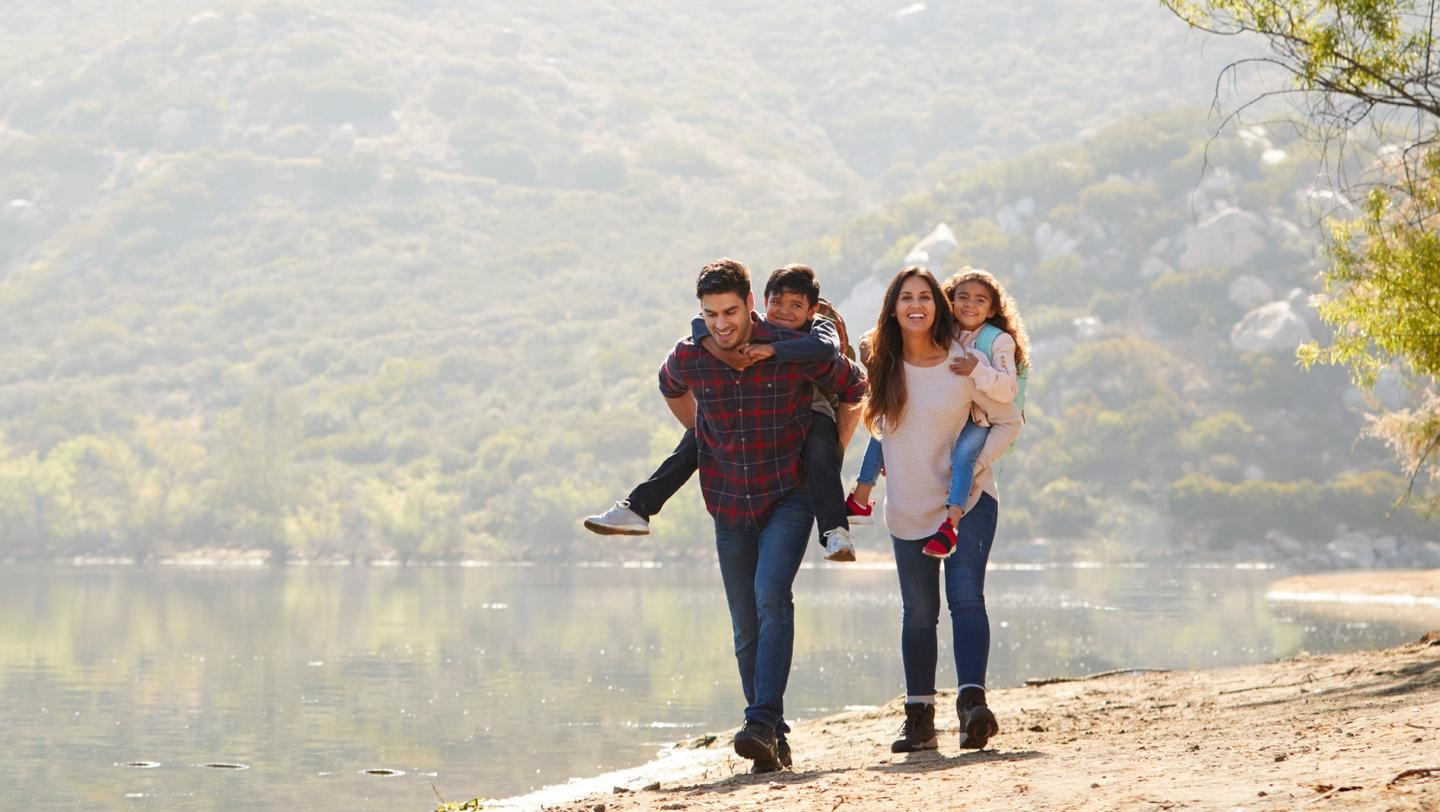 Parents piggybacking their young children by a mountain lake