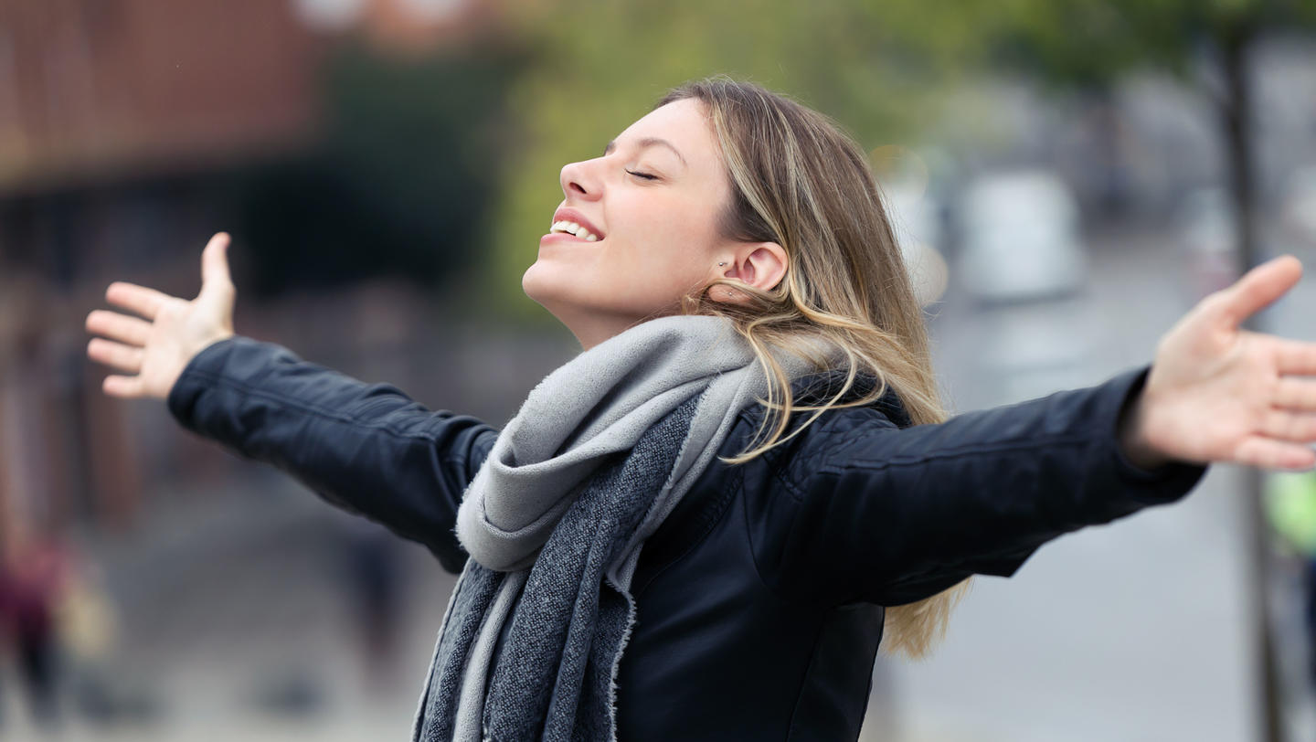 Smiling young woman breathing fresh air and raising arms in the city.