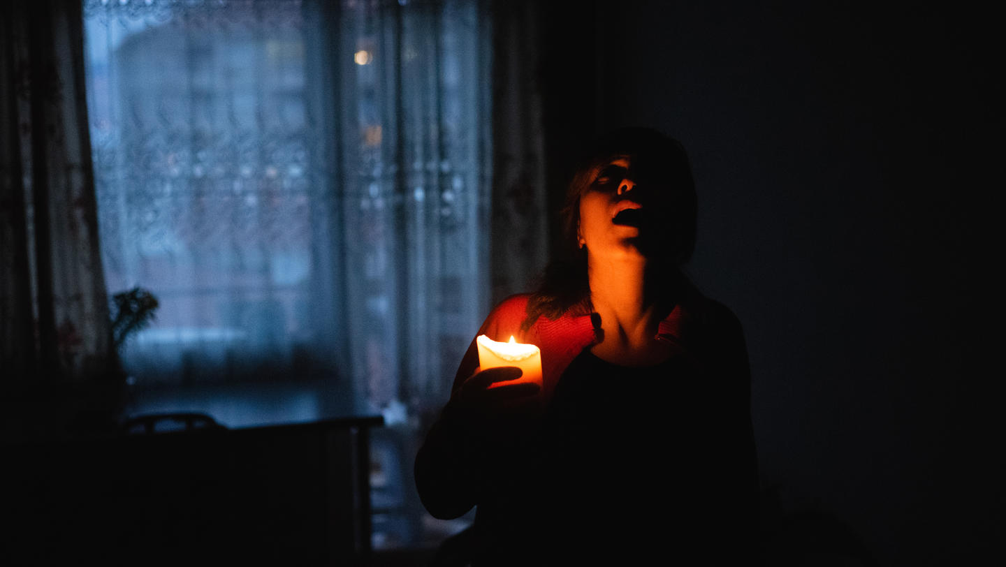 Woman with candle at home because of power cut