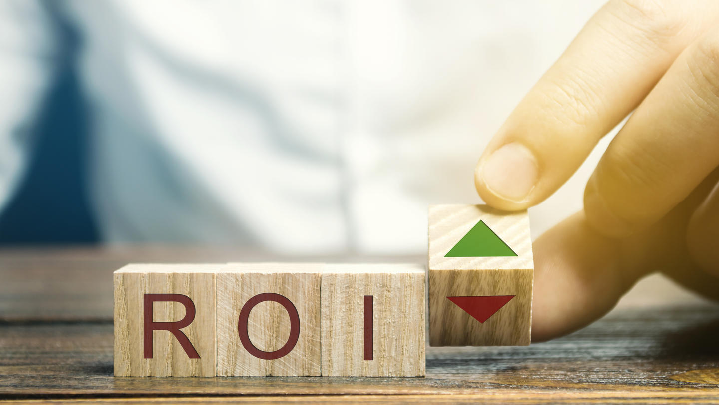 Wooden blocks with the word ROI and green arrow up. High level of business profitability. Return on investment, invested capital, rate. Success. Growth. Analytics. Report