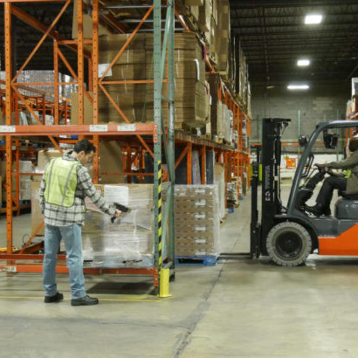 Warehouse with man scanning inventory and another operating a forklift