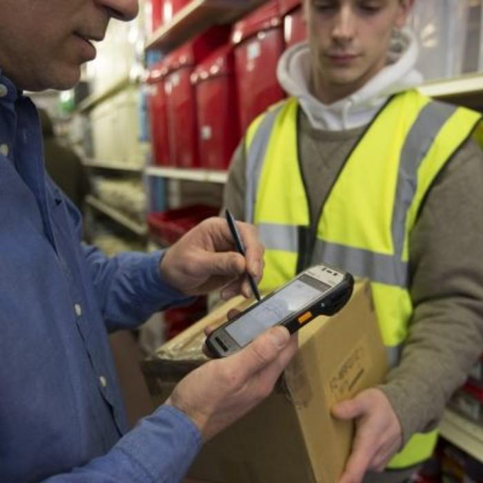 Man uses a Panasonic Android handheld to sign for a package