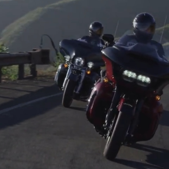 two motorcyclists riding along a scenic highway